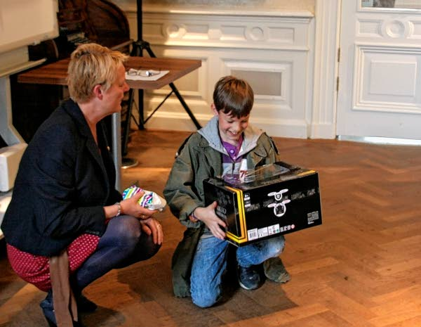 De winnaar van de AW-Jeugdprijsvraag ontvangt zijn prijs uit handen van marsleider Wilma Luckel